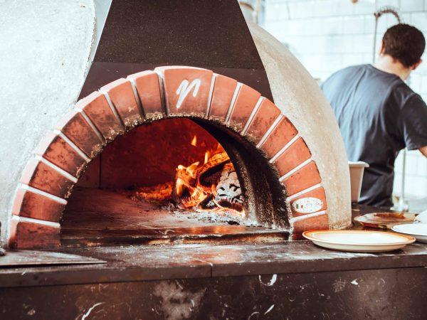 Die original italienische Pizza wird in einem Steinofen gebacken und mit einer Holzschaufel aus dem heißen Ofen geholt, so verhindert der Bäcker sich die Hände zu verbrennen. (Foto: Cathal Mac an Bheatha/ unsplash.com)
