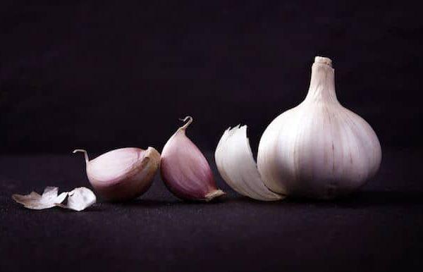 """Durch das Quetschen der Knoblauchzehen in einer Knoblauchpresse werden die einzelnen Pflanzenzellen """"zerpresst"""". Dadurch erscheint der Geschmack durch das Pressen intensiver als durch das Schneiden der Knolle."""