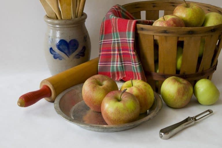 Äpfel auf Teller und in Schale mit Schäler und Teigroller