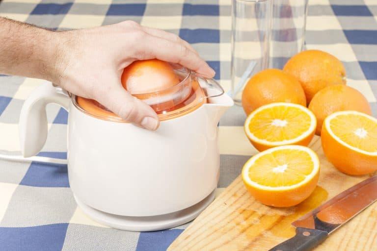 Hand presst Orangen mit Fruchtpresse