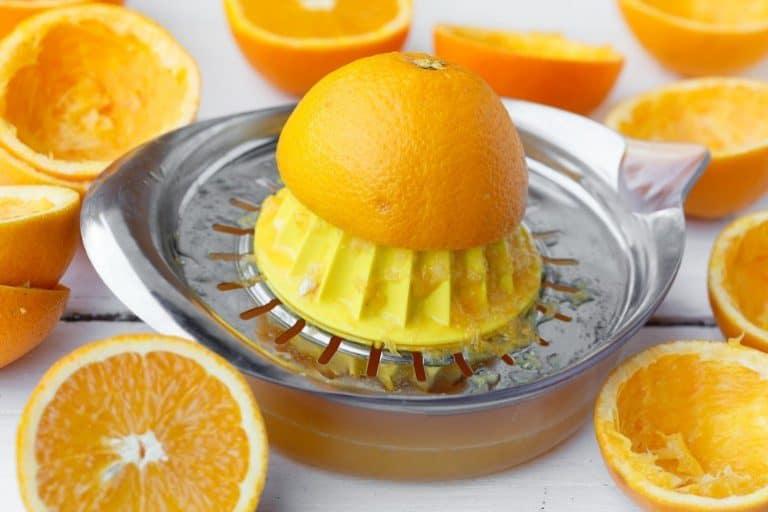 Kleine manuelle Orangenpresse aus Plastik mit Auffangbehälter. Viele bereits gepresste Orangenhälften auf der Bildseite.