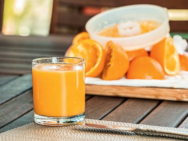 Frisch gepresster Orangensaft mit Orangenpresse und ausgepressten Orangenhälften im Hintergrund