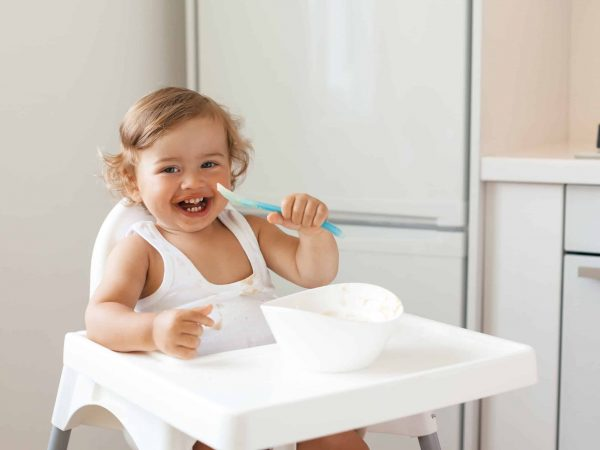 Cute baby 1,4 years old sitting on high children chair and eating vegetable alone in white kitchen