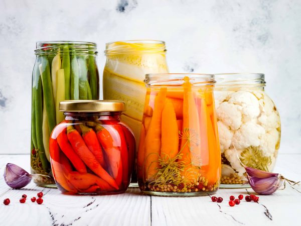 Marinated pickles variety preserving jars. Homemade green beans, squash, cauliflower, carrots, red chili peppers pickles. Fermented food.