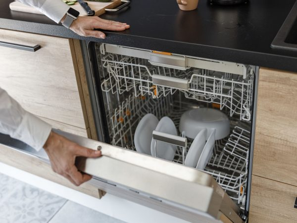 Woman is opening the dishwasher in the kitchen